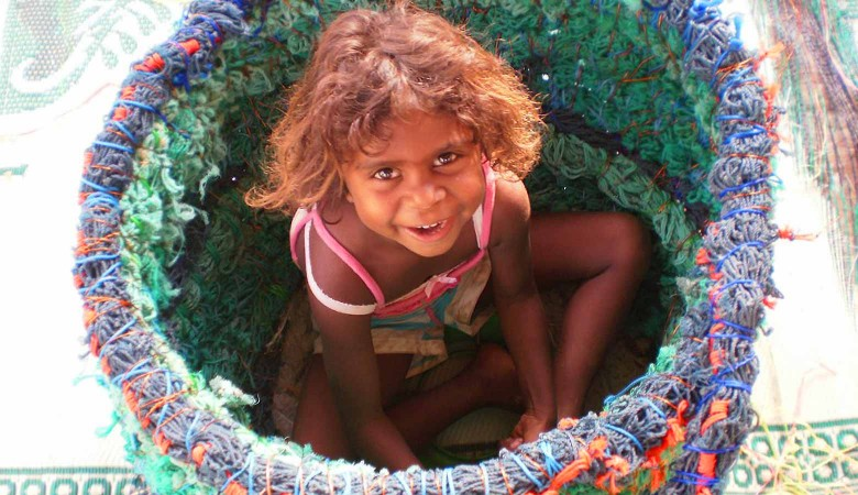 Photo by Sue Ryan. Shekeena Pahimbung easily fits into this basket as it was being made during the first ghost net workshop in Aurukun in 2009.